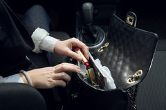 Closeup shot of female driver searching for lipstick in purse Stock Photography