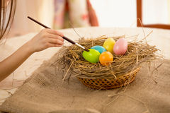 Closeup shot of girl holding paintbrush coloring Easter eggs Royalty Free Stock Photography