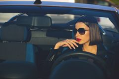 Closeup shot of glamor brunette girl with red lips wearing sunglasses driving a cabriolet. Empty space stock image