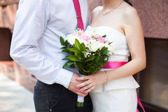 Closeup shot of groom and bride. Hugging and holding bouquet of white and pink roses Royalty Free Stock Photography