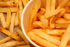 Paper cup filled with French fries. Half of the cup is seen on the photo. Surrounded by crispy French fries on a baking sheet. royalty free stock image