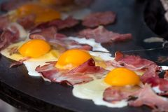 English breakfast, frying ham and egs on a big grill pan. Closeup shot of ham and eggs on a big frying pan being cooked outdoor. English breakfast Royalty Free Stock Photo