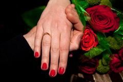 Closeup shot of hands. Closeup shot of holding female with engagement ring and male hands with red roses bouquet on background indoors Royalty Free Stock Photos
