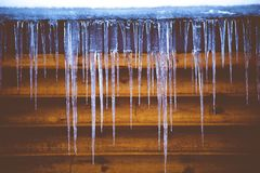 Closeup shot of ice cycles with a wooden wall in the background