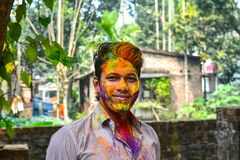 Closeup shot of Indian young man covered with multi color dry paint at Holi Festival. royalty free stock image