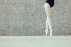 Closeup of legs of ballet dancer standing in pointes. Closeup shot of legs of a female ballet dancer standing on her toes wearing pointe shoes. Ballet dancer Royalty Free Stock Photos