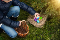 Closeup shot of little girl putting painted egg in basket Royalty Free Stock Photo