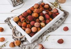 Closeup shot of lychees in wooden box. On white table royalty free stock photos
