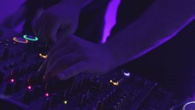 Closeup shot of male dj hands turning controls on sound equipment at club party. Stock footage stock video