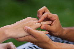 Closeup shot of male and female hands. Groom is putting engagement ring with diamond on bride's hand outdoors Royalty Free Stock Photos