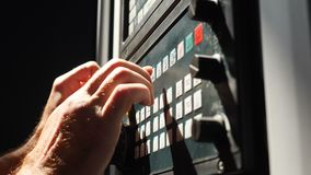 Closeup shot of male hands pushing buttons on industrial equipment. Engineer controlling automated production line