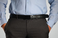 Closeup Shot of Male Waist with Hands in Pocket. Photo image closeup shot of male waist with hands in pocket dressed in black pants, belt, blue shirt. Formal Royalty Free Stock Photo