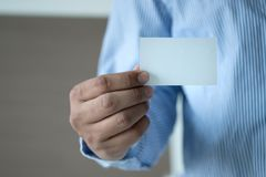 Closeup shot  Man show white business card Plastic bank-card des. Ign mock up Royalty Free Stock Image