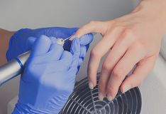 Closeup shot of manicurist in blue rubber gloves cleans cuticle on female nails using a milling cutter for manicure Stock Images
