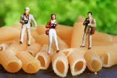 Food photographers. Closeup shot of miniature photographers standing on penne pasta stock photography