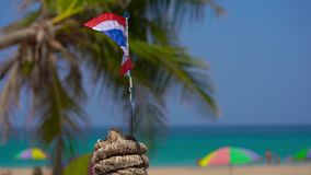 Closeup shot of a national flag of Thailand on a beautiful beach. Tropical vacation concept. Travel to thailand concept.  stock video footage