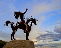 Silhouetted Native Sculpture in Osoyoos, British Columbia, Canada. Closeup shot of native sculpture making offering during sunset in southwestern Canada Royalty Free Stock Image