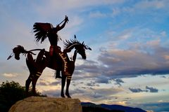 Silhouetted Native Sculpture in Osoyoos, British Columbia, Canada. Closeup shot of native sculpture making offering during sunset in southwestern Canada Royalty Free Stock Photography