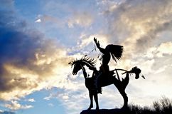 Silhouetted Native Sculpture in Osoyoos, British Columbia, Canada. Closeup shot of native sculpture making offering during sunset in southwestern Canada Royalty Free Stock Images
