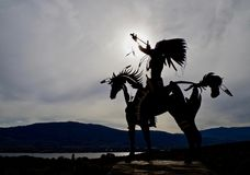 Silhouetted Native Sculpture in Osoyoos, British Columbia, Canada. Closeup shot of native sculpture making offering during sunset in southwestern Canada Stock Photo