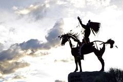 Silhouetted Native Sculpture in Osoyoos, British Columbia, Canada. Closeup shot of native sculpture making offering during sunset in southwestern Canada Royalty Free Stock Photo