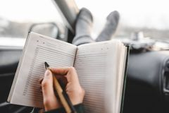 Closeup shot of notebook and pen in hands. Inside the car. Ready to write stock photos