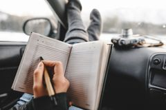 Closeup shot of notebook and pen in hands. Inside the car. Ready to write. Making a plan of trip royalty free stock images