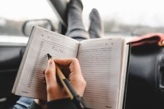 Closeup shot of notebook and pen in hands. Inside the car. Ready to write. Making a plan of trip royalty free stock photos