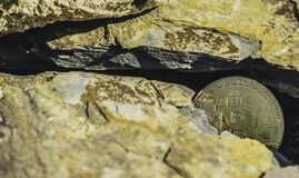 Free Closeup Shot Of A Golden Coin With Engraved Bitcoin Logo, Lying On The Ground Among  Rocks Royalty Free Stock Photos - 181414138