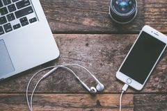 Free Closeup Shot Of A Laptop With A Smartphone And Headphones On A Wooden Background And A Camera Lens Stock Photos - 156133673