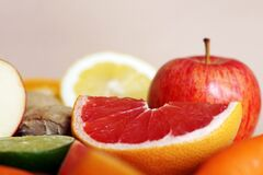 Free Closeup Shot Of Red Apple Lemons Oranges And Grapefruit Slices On A Beige Background Stock Photos - 181320243