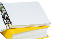 Closeup shot of opened yellow copybook on book. Stock Photo