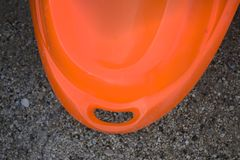 A closeup shot of an orange flat board with an opening to hang it on a hook. It looks like a standing board for a water sport with stock image