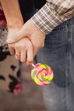 Closeup shot of pair is holding hands. And bright candy Royalty Free Stock Photography