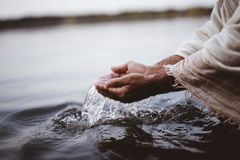 Closeup shot of a person`s hands holding water with a blurred background