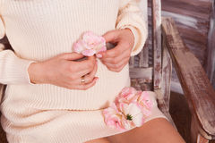 Closeup shot of pregnant woman belly. With pink flovers in her hands dressed in beige knitted dress Royalty Free Stock Photo