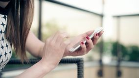 Closeup shot of redhead female hands holding smartphone, typing text on touch screen. Woman answering friend message in. Social network application, searching stock video footage