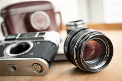 Closeup shot of retro camera, lens and leather case lying on tab Royalty Free Stock Images