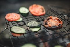 Cooking tomatoes and cucumbers at the stake. Closeup shot of roasted tomatoes and cucumbers at the stake stock image