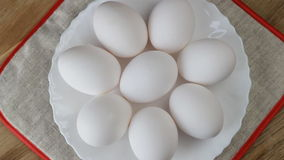 Closeup shot of a rotating pile of fresh chicken eggs on white plate. HD stock video footage