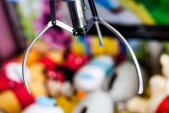 Closeup Shot of Slot Machine Toy Crane in Amusement Park. Electronic Arcade Claw Gripper Game for Grabbing Stuffed as a stock photography