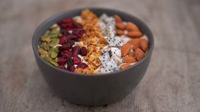 Closeup shot of a smoothie bowl with papaya, dragon fruit, granola, dried cherry, and pumpkin seeds. Healthy breakfast. Concept stock video