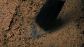 Excavating Dinosaur Claw Fossil. Closeup shot of someone excavating a fossilized dinosaur claw in the ground stock video footage