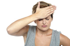 Closeup shot of a stressed out lady. With hand on her forehead. All on white background Royalty Free Stock Photo