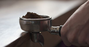 Closeup shot of tamping fresh ground coffee for preparing espresso Royalty Free Stock Image