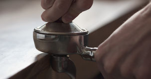 Closeup shot of tamping fresh ground coffee for preparing espresso Royalty Free Stock Photo