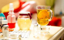 Closeup shot of tea and medicines on table next to bed Royalty Free Stock Images