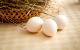 Closeup shot of three white eggs lying on table next to basket Royalty Free Stock Photography