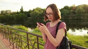 Student girl using smartphone standing outdoors on the bridge. Hipster browsing Internet on a phone, texting and. Closeup shot of tudent girl using smartphone stock video