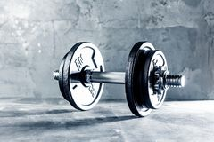 Closeup shot of two dumbells placed on dark Grey surface. stock image